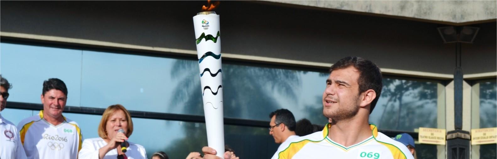 Imagem de um jovem segurando a tocha olímpica.